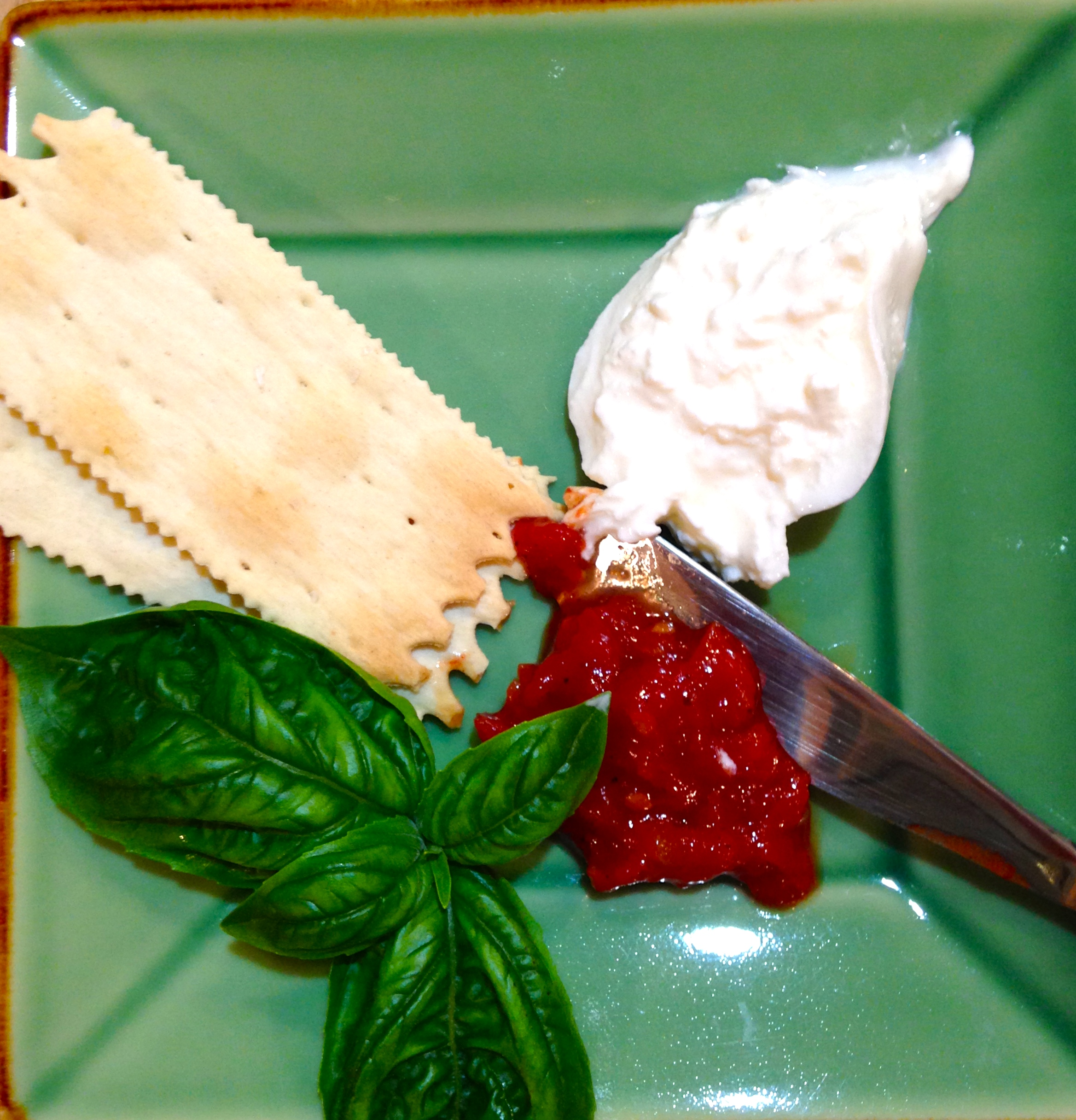 a new caprese plate of mozzarella, crackers and jam and basil