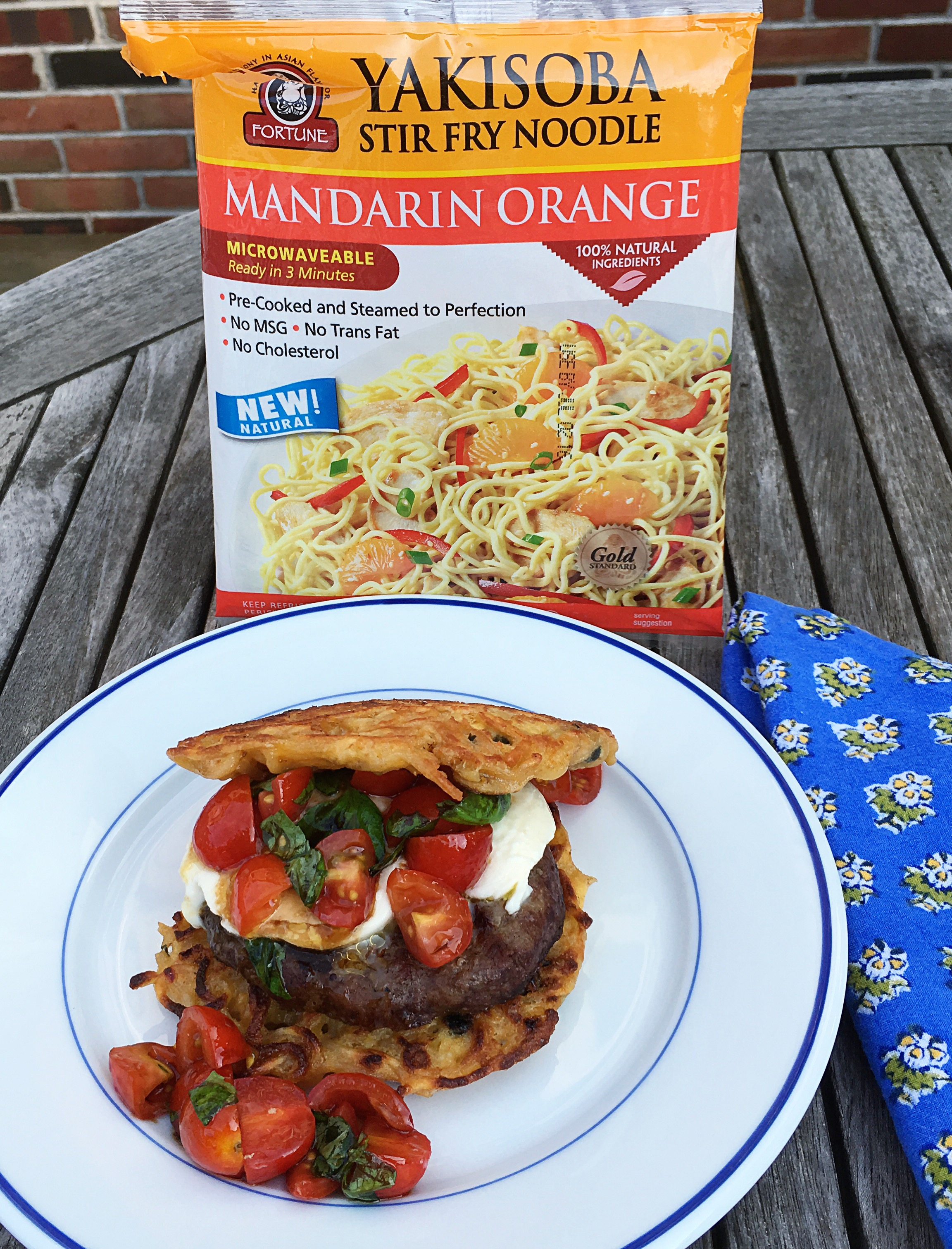 burger on noodle bun with tomatoes and cheese