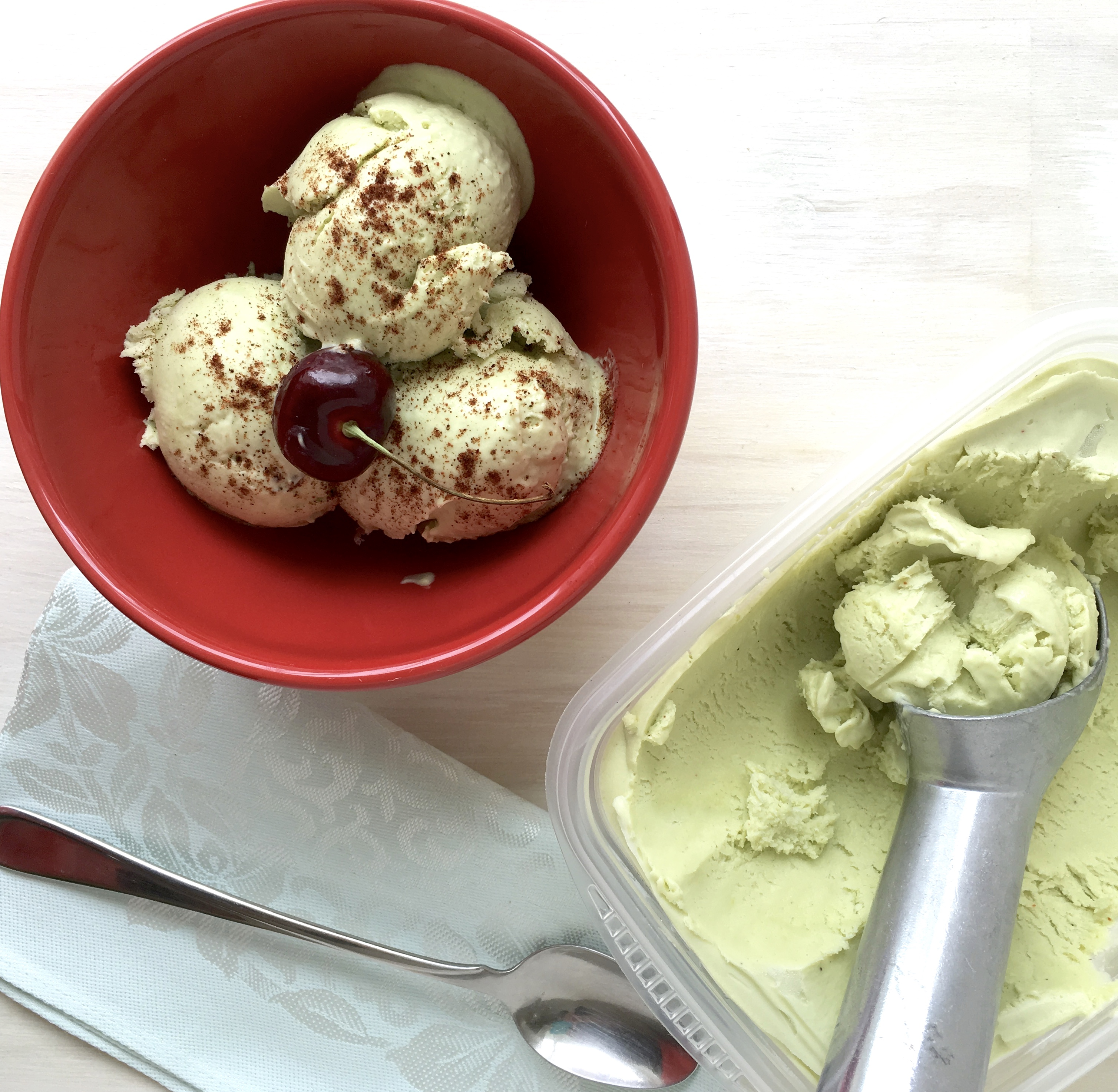 scoop of avocado ice cream in a bowl with chili powder and cherry