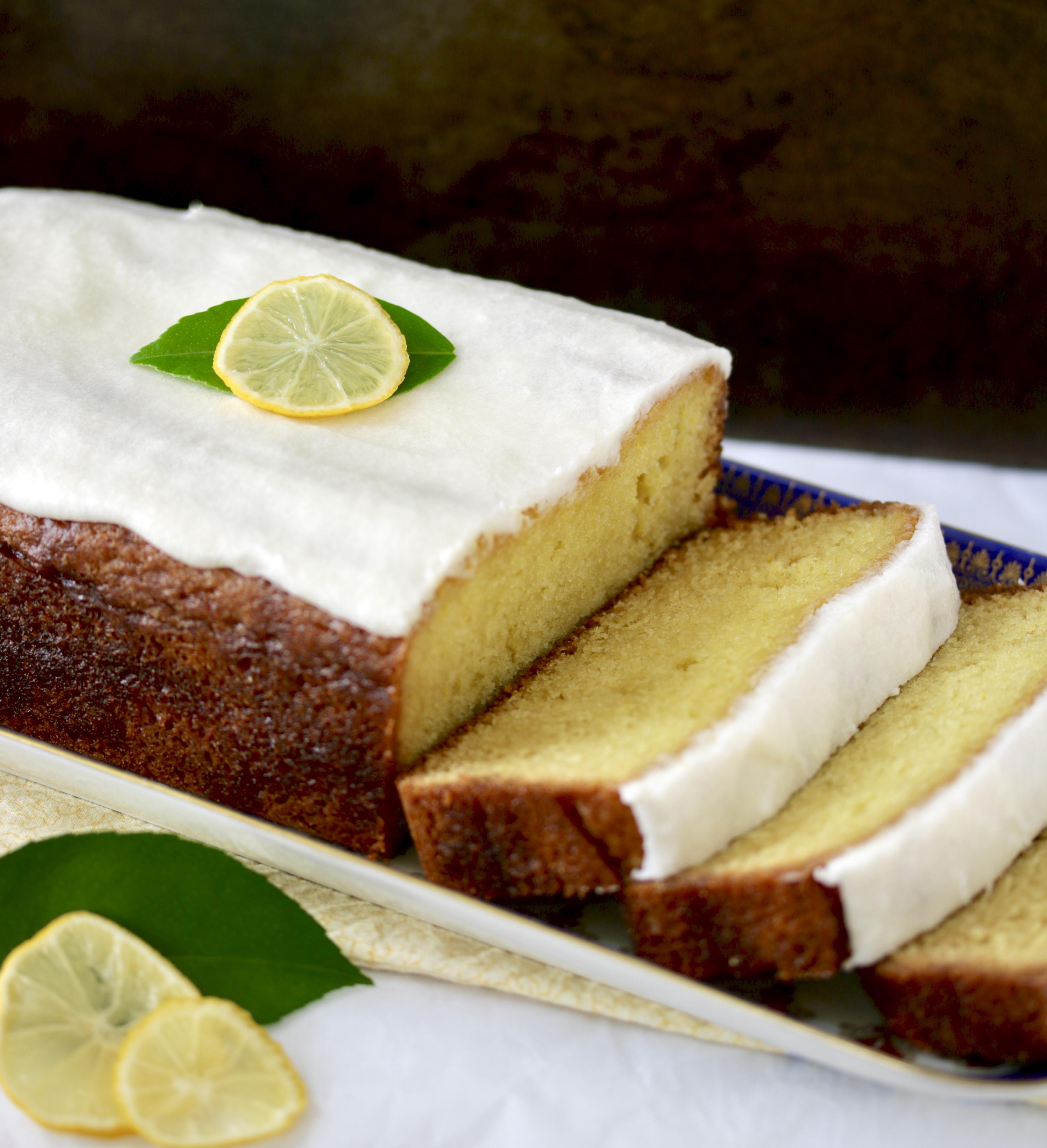 sliced lemon loaf with white icing and lemon slice garnish