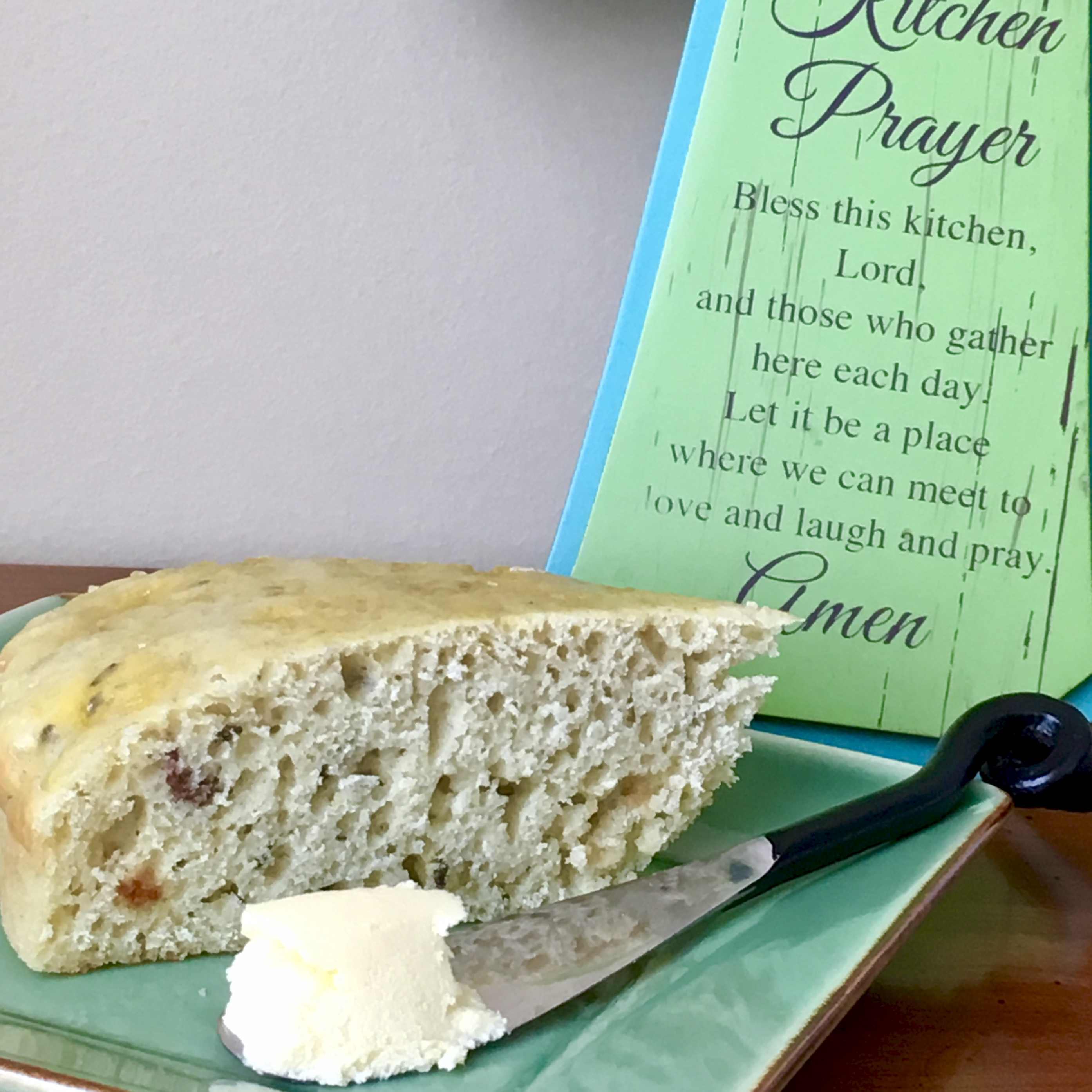 Irish soda bread plated with butter and Kitchen prayer