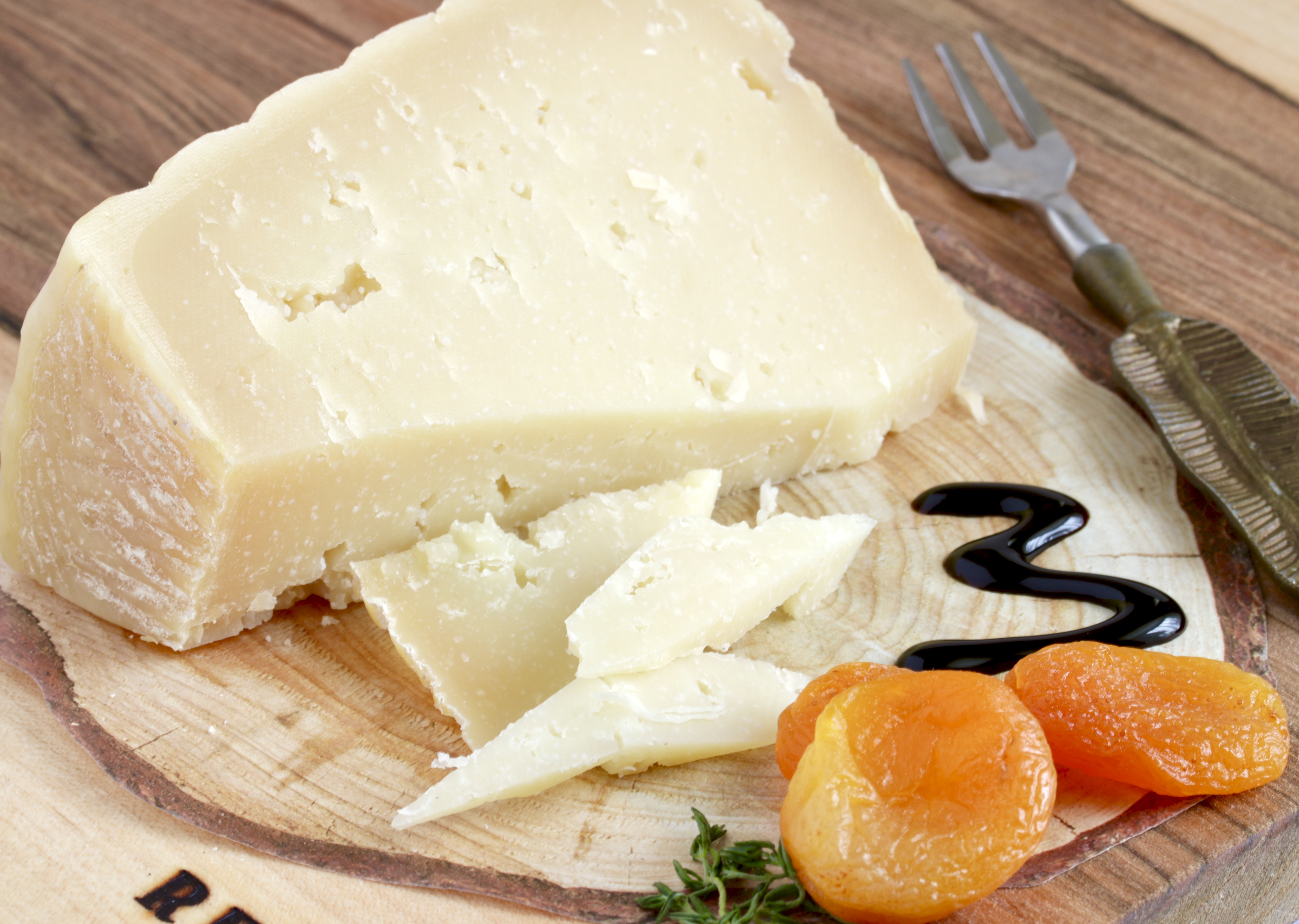 serving of cheese and dried apricots with balsamic glaze