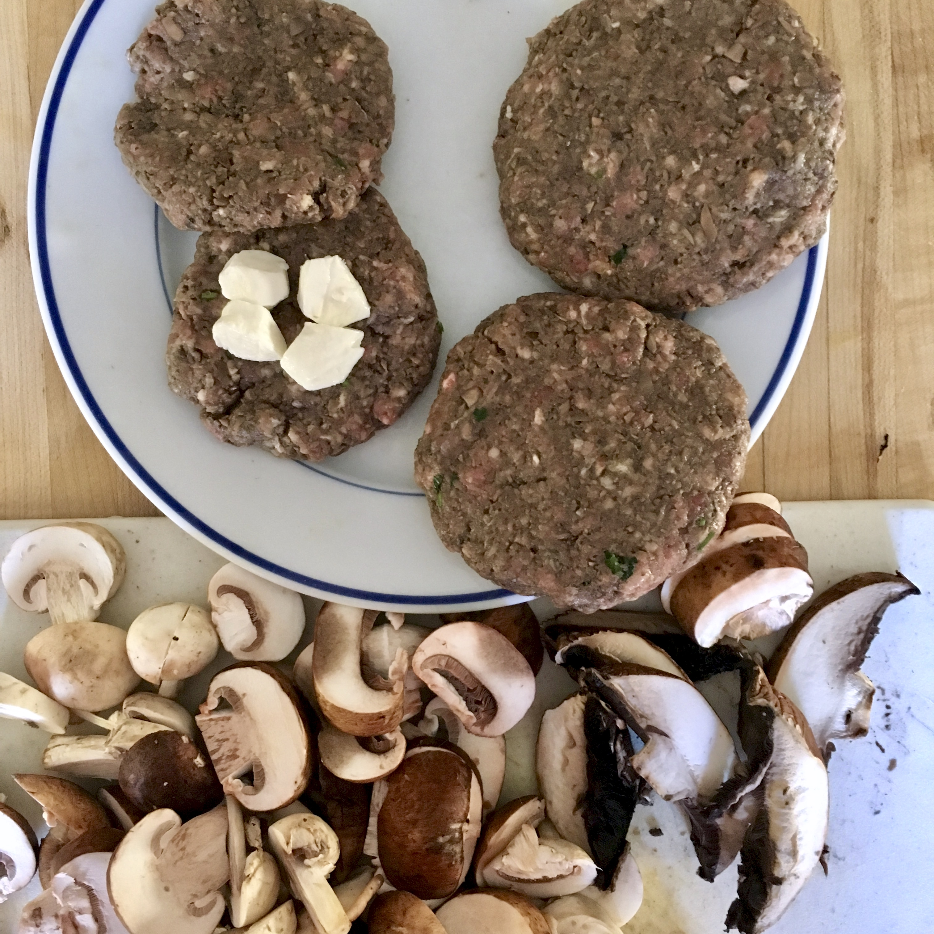 raw burgers with cheese and mushrooms