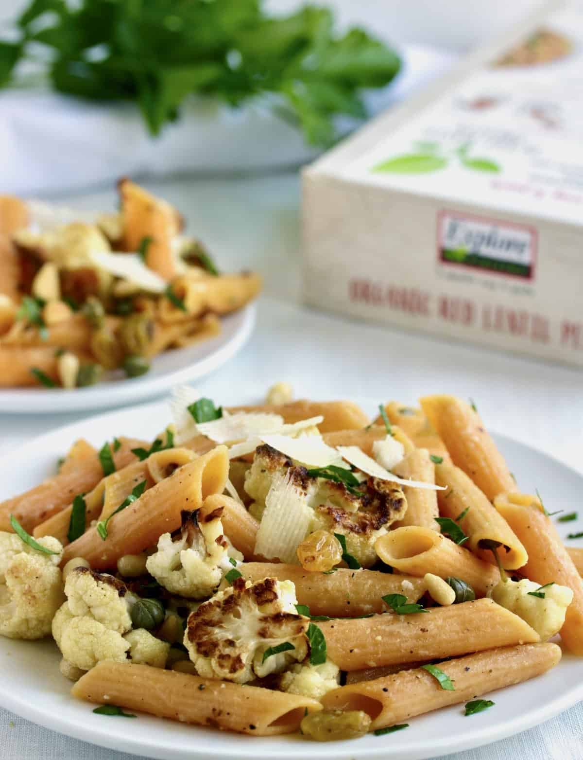 plates of penne pasta with cauliflower, herbs and product package