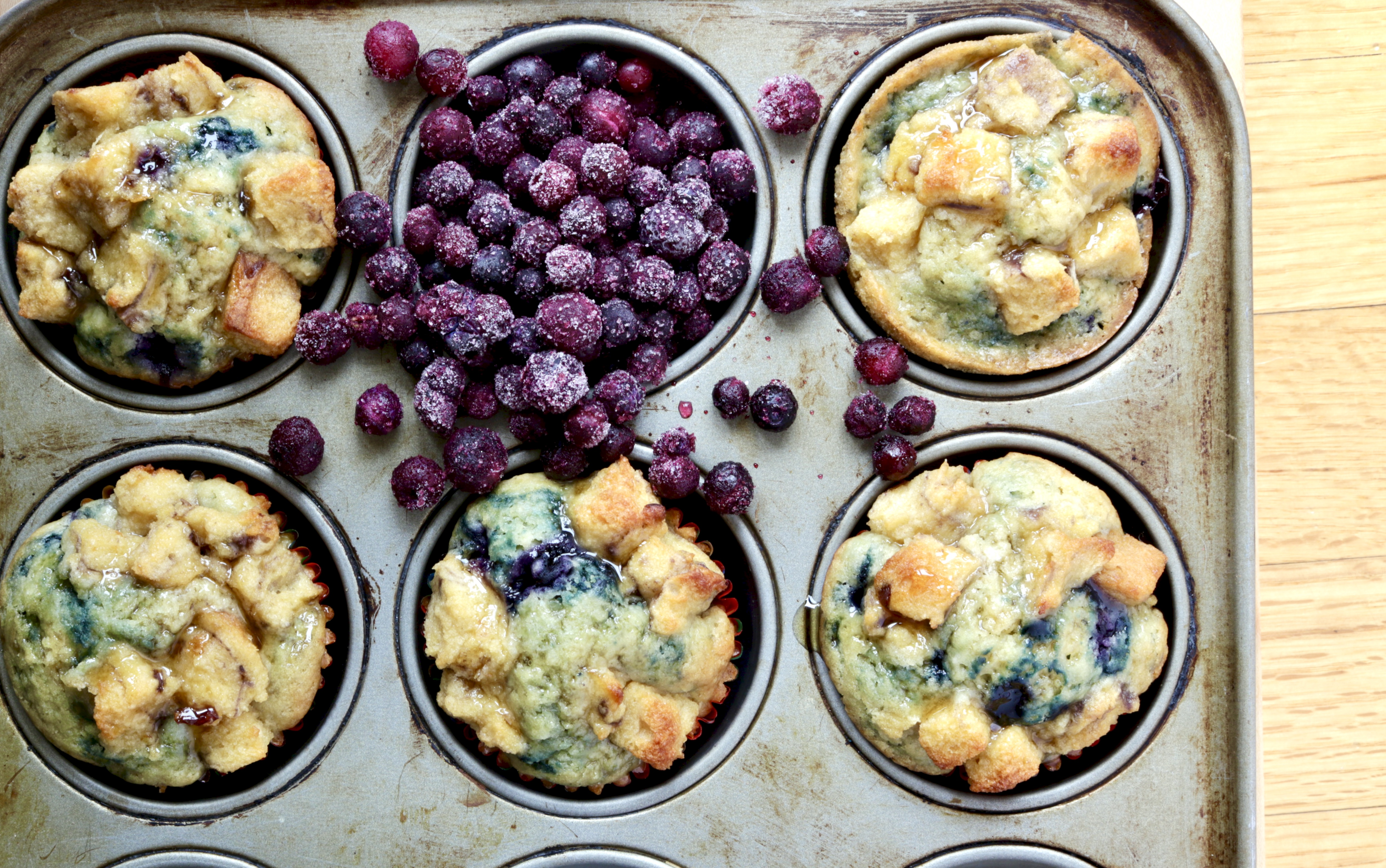 maple blueberry French toast muffins in muffin tin with wild blueberries spilling over