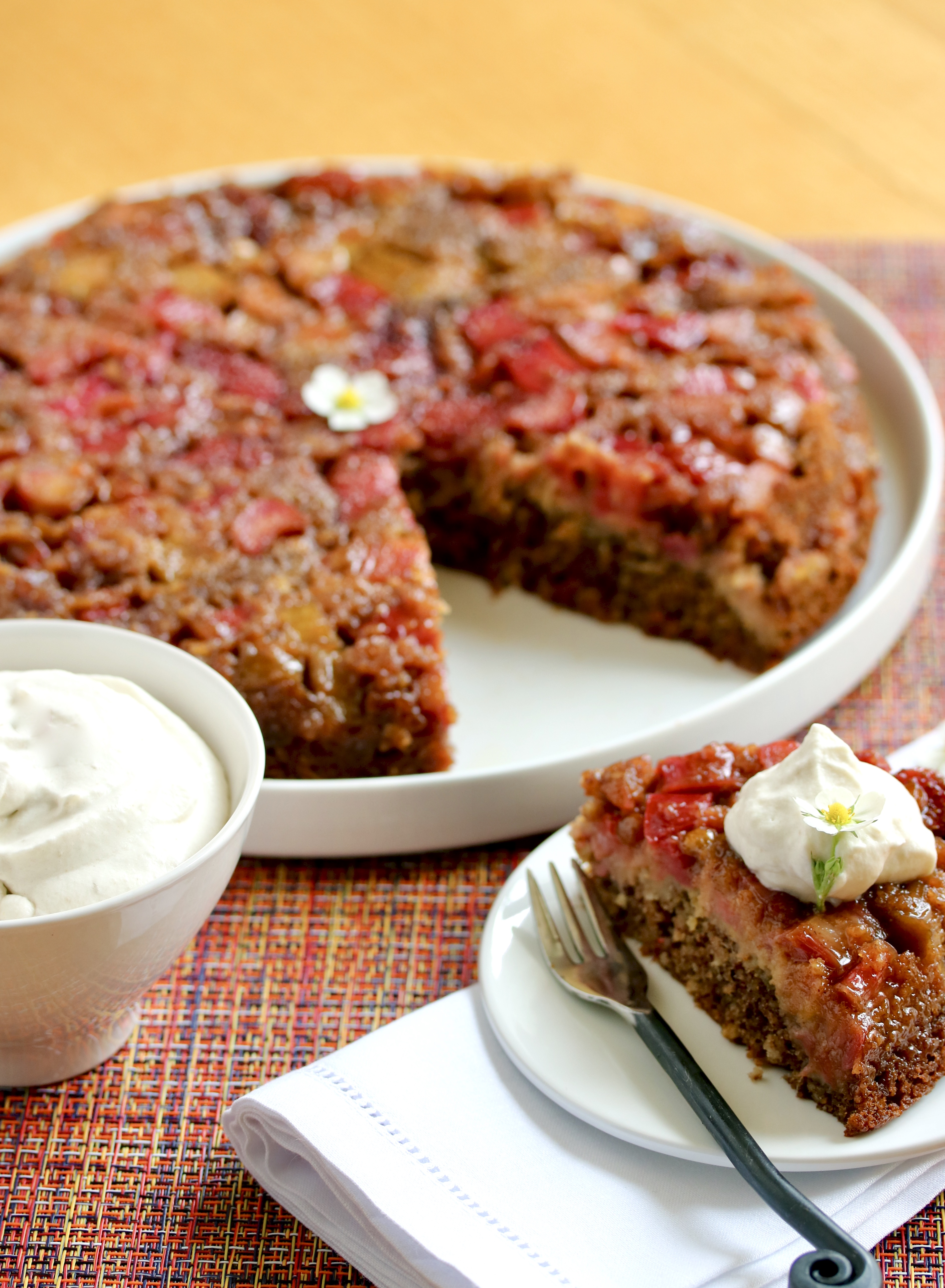 strawberry rhubarb skillet cake with slice cut out and bowl of whipped cream