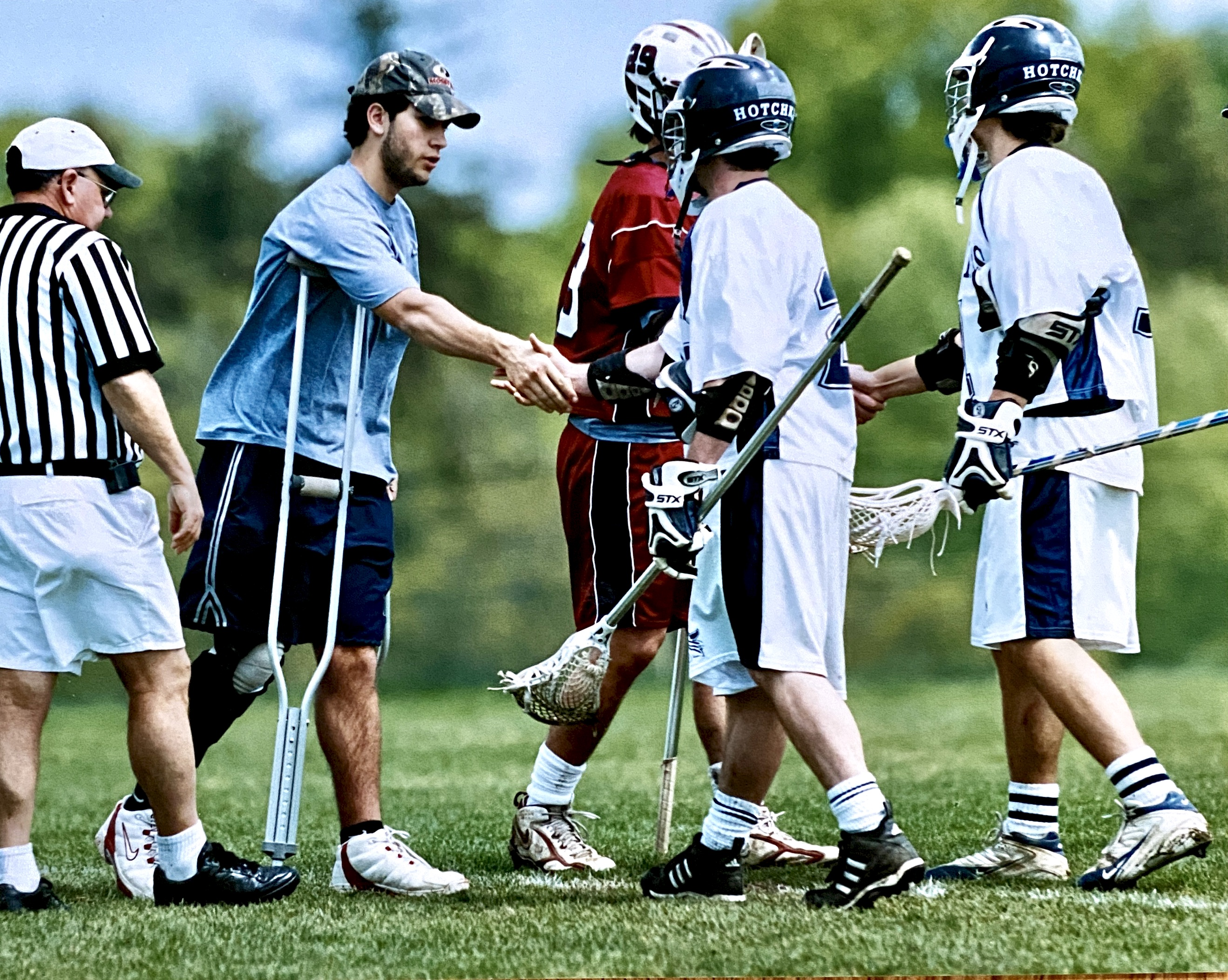 my son post knee injury on lacrosse filed shaking hands with opposing team
