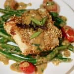 roasted sesame cod on a plate with green beans, cherry tomatoes and lemon grass basil sauce