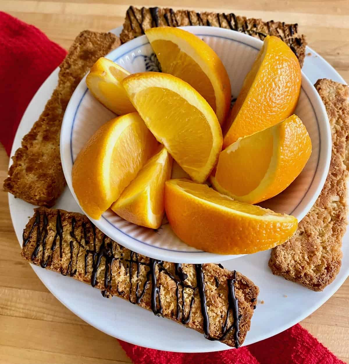 toasted coconut biscotti with chocolate espresso drizzle on plate with oranges