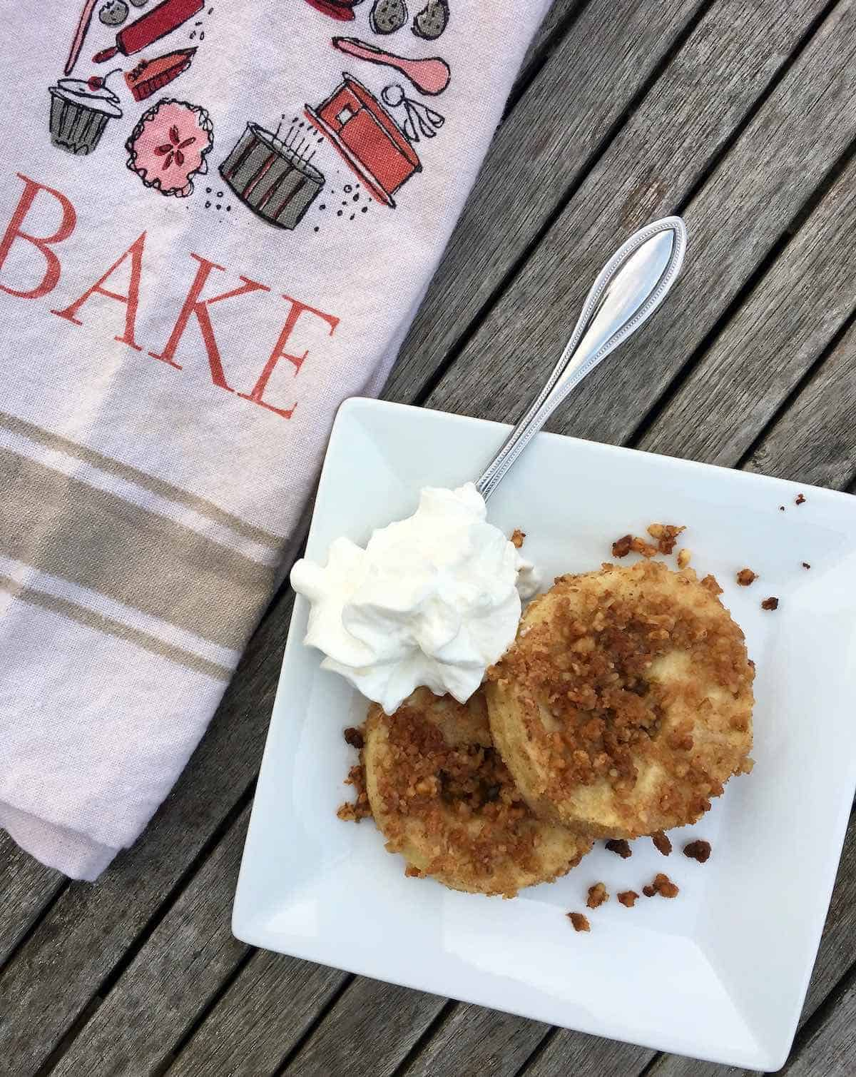 plated apple crisp slices with a tea towel that says BAKE