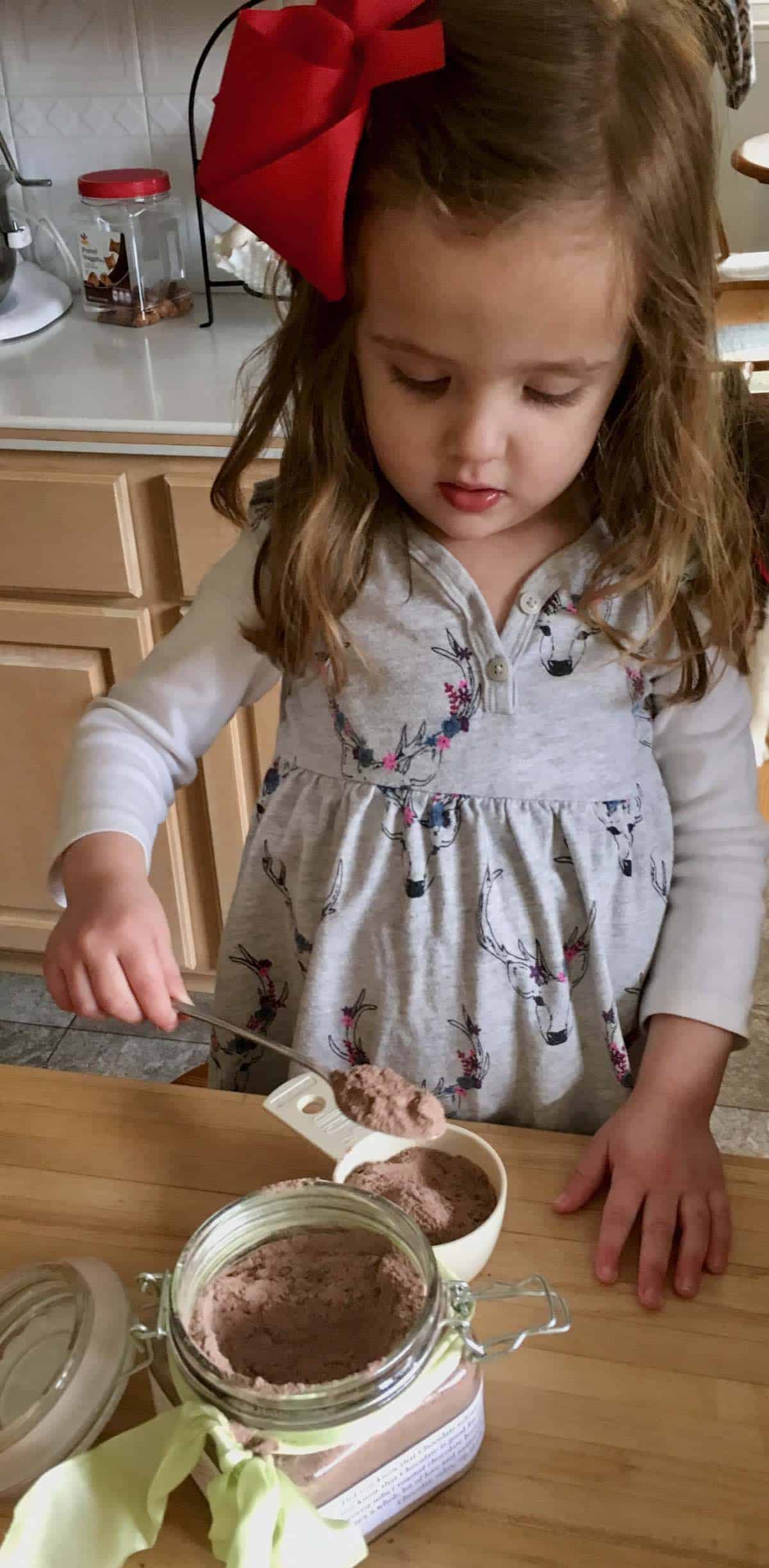 my grand daughter spooning the most decadent hot chocolate mix
