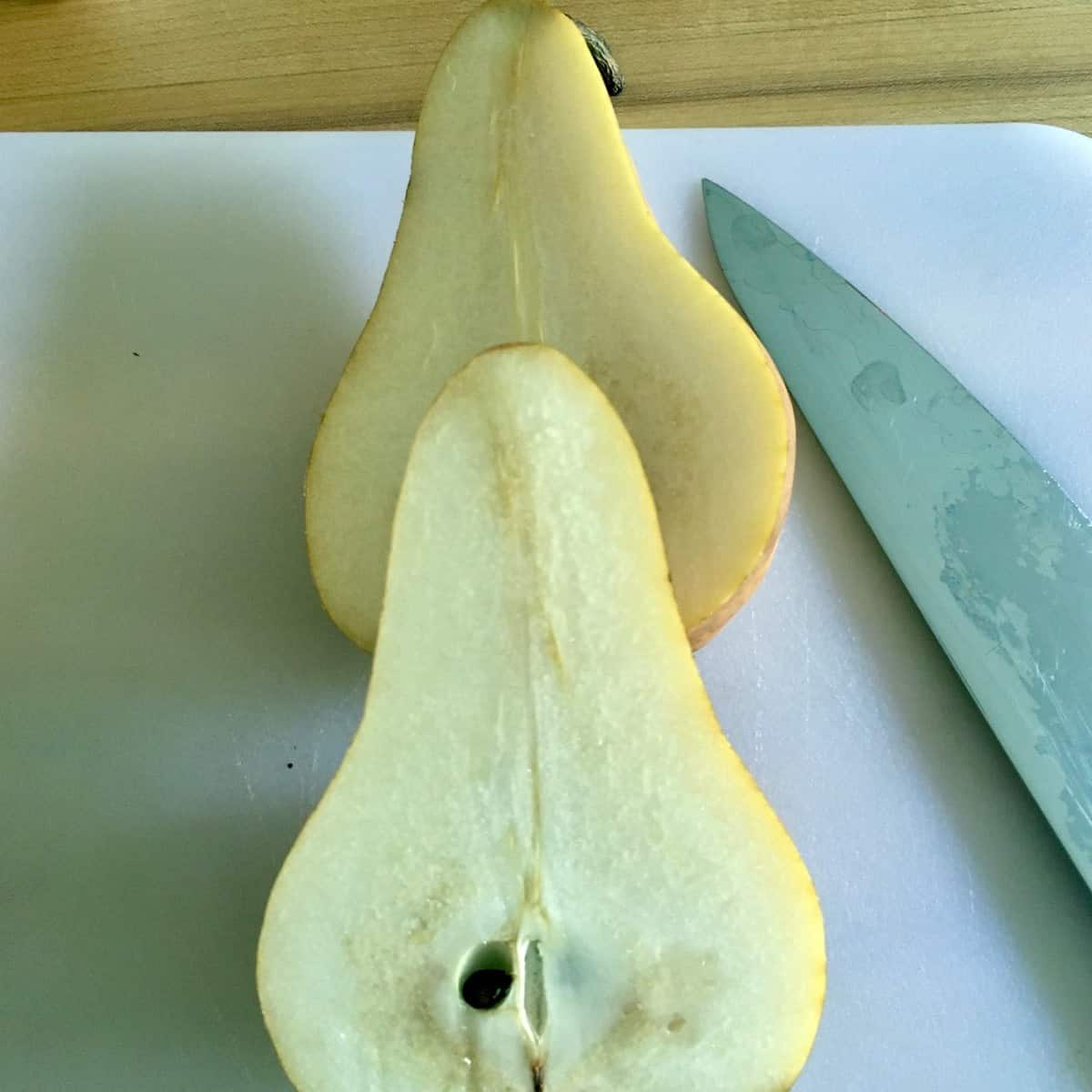 sliced pear with knife on cutting board prepping for salted chocolate pear pound cake