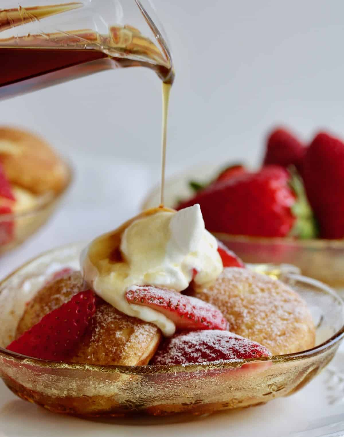 strawberry stuffed pancakes in bowl with sliced strawberries, cream and syrup poured on top