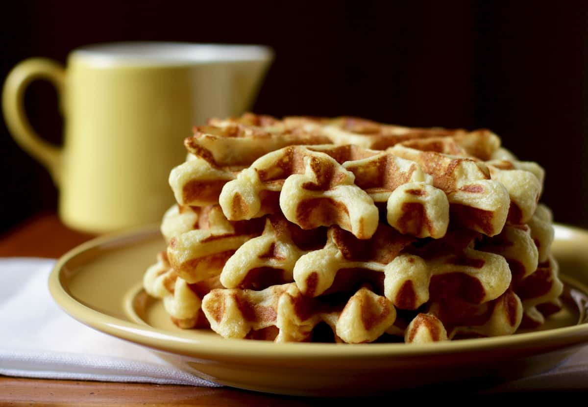 stack of waffles with yellow syrup pitcher