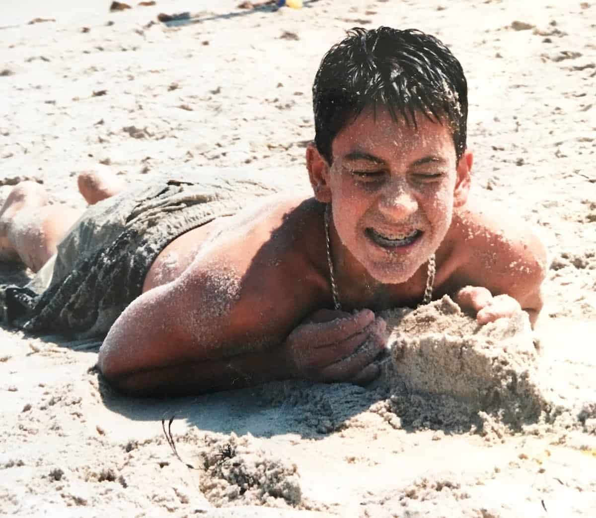 my young son at the beach covered in sand