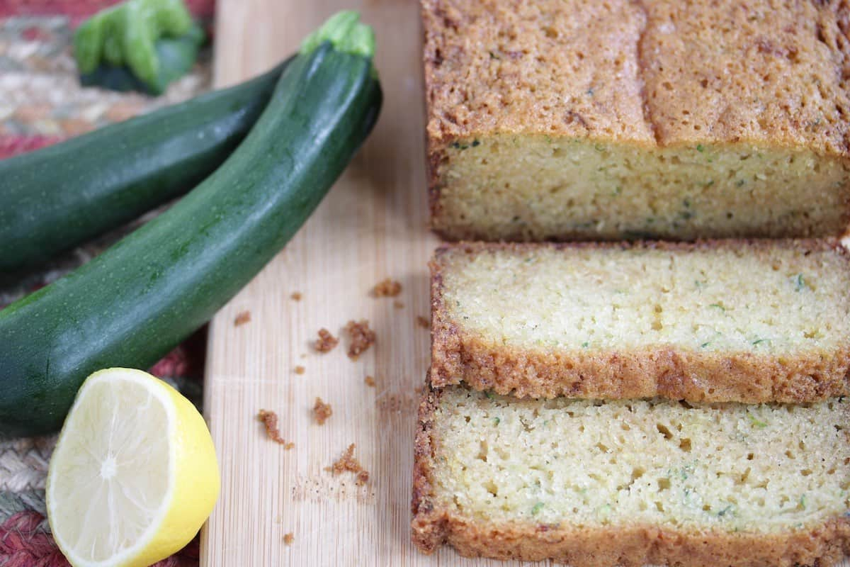 sliced zucchini bread with fresh cut lemon and zucchini on cutting board