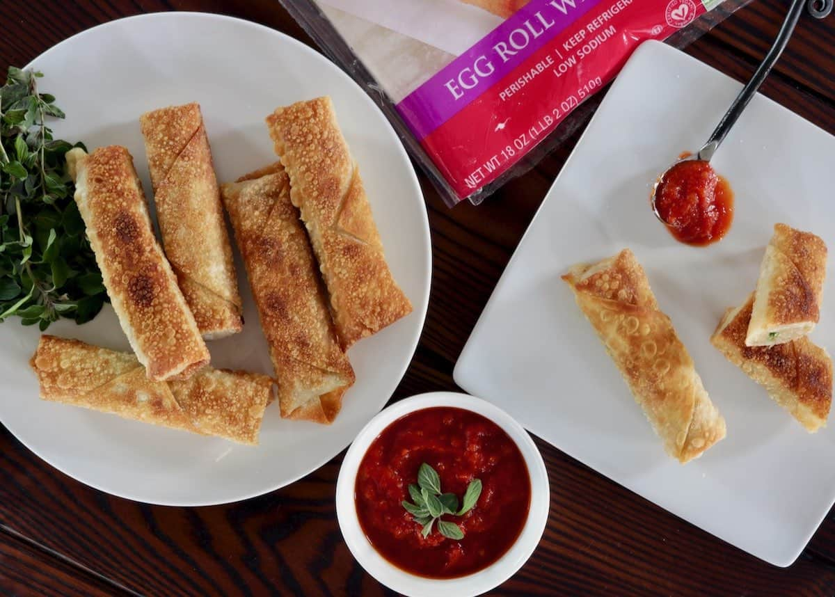 overhead view of egg rolls and sauce on white plates
