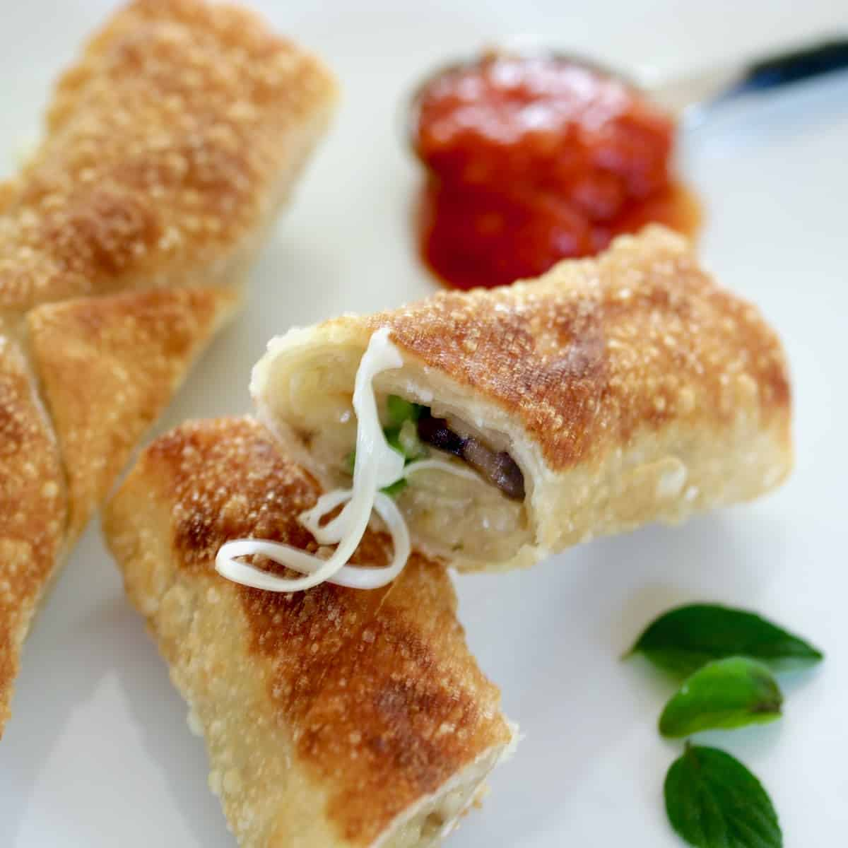 sliced egg rolls with sauce and herbs