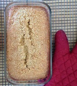 coconut loaf cake on cooling rack with red potholder