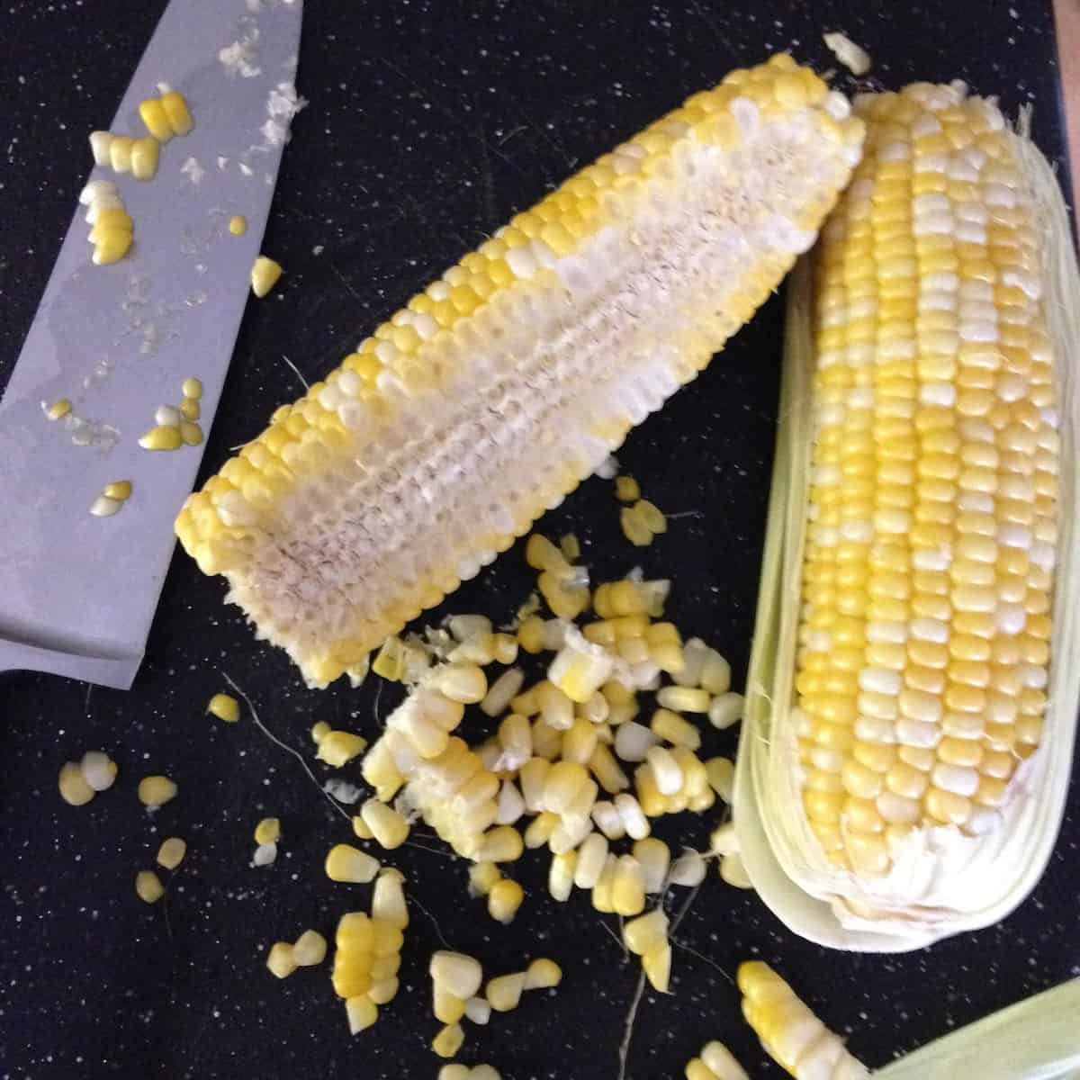 cutting fresh corn off the cob for caramel corn cupcakes