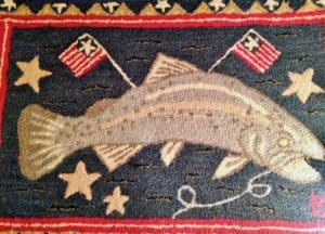 hooked rug with fish and flags