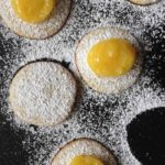 lemon curd on cookies dusted with powdered sugar