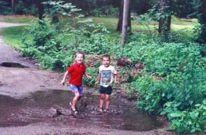 two kids playing in the mud