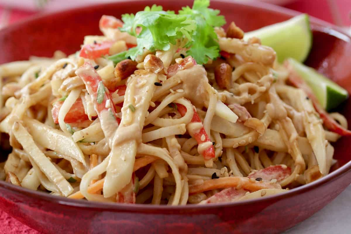 pear pad Thai salad served in red bowl garnished with lime and cilantro
