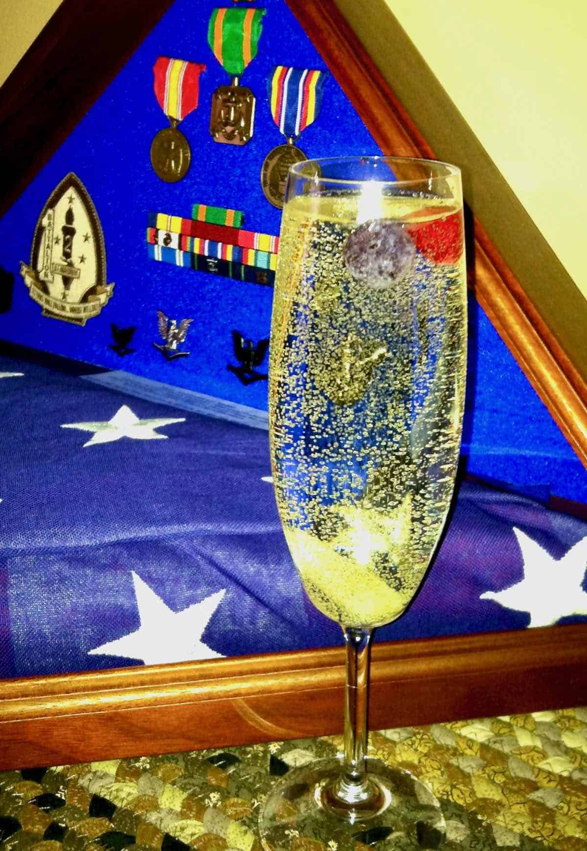 his flag, medals and a sparkling cocktail