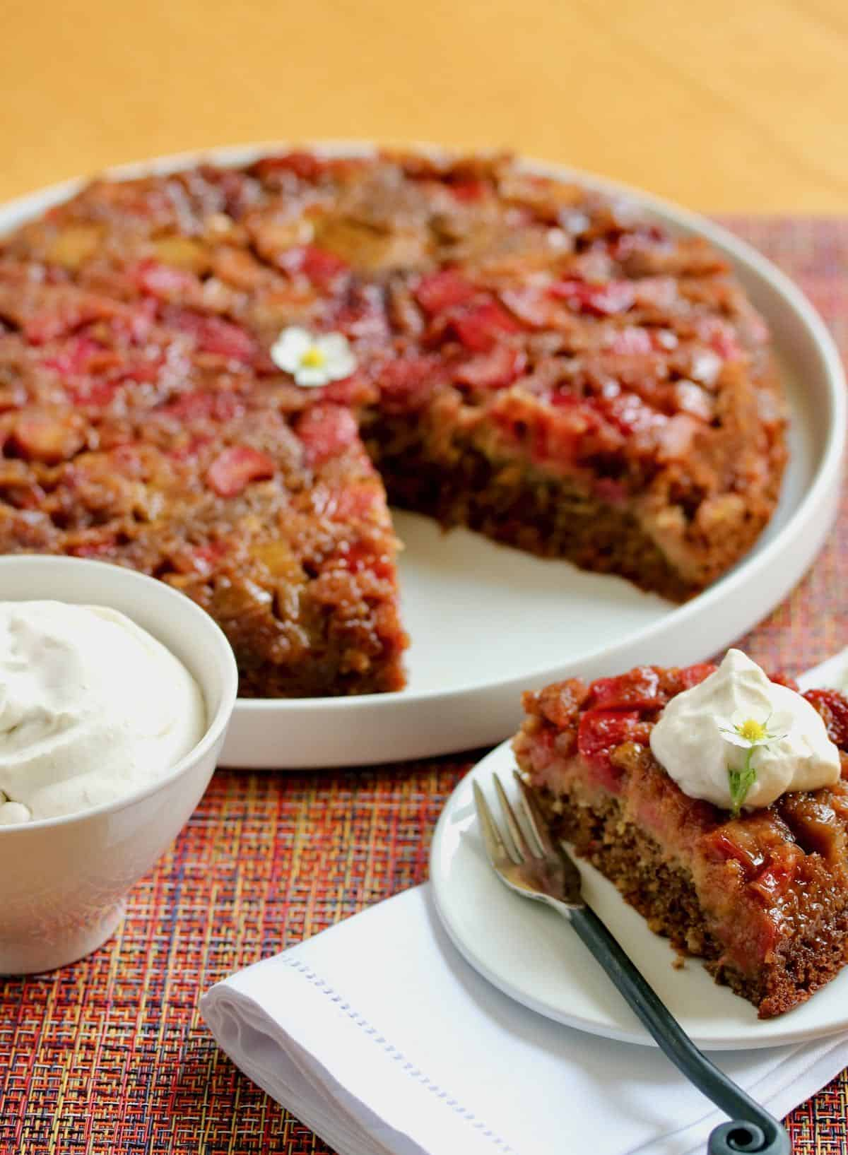 strawberry rhubarb skillet cake sliced with bowl whipped cream. one of my winning recipes