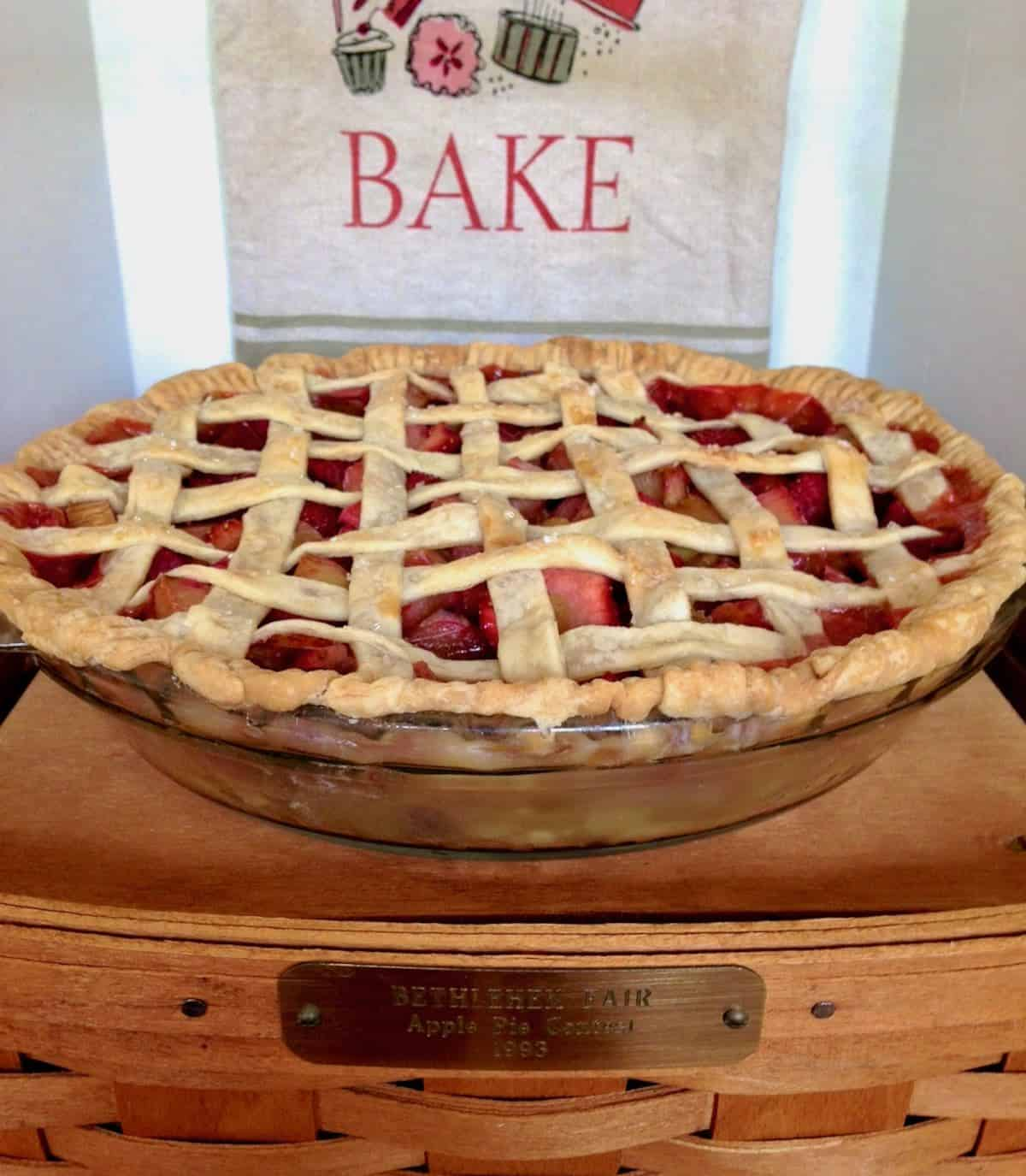 strawberry rhubarb pie sitting on a basket with a tea towel that says BAKE