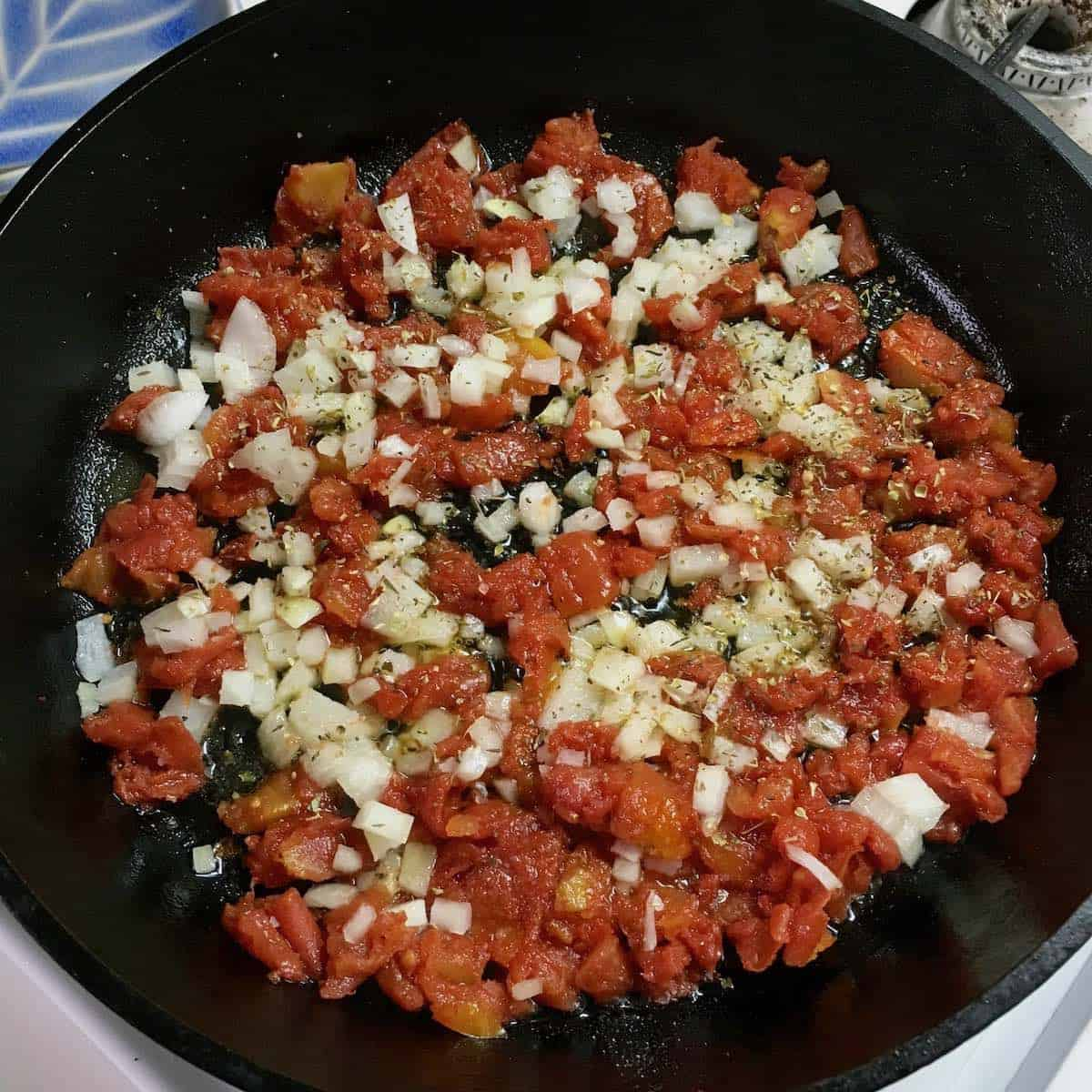 cooked tomatoes and onions in cast iron pan