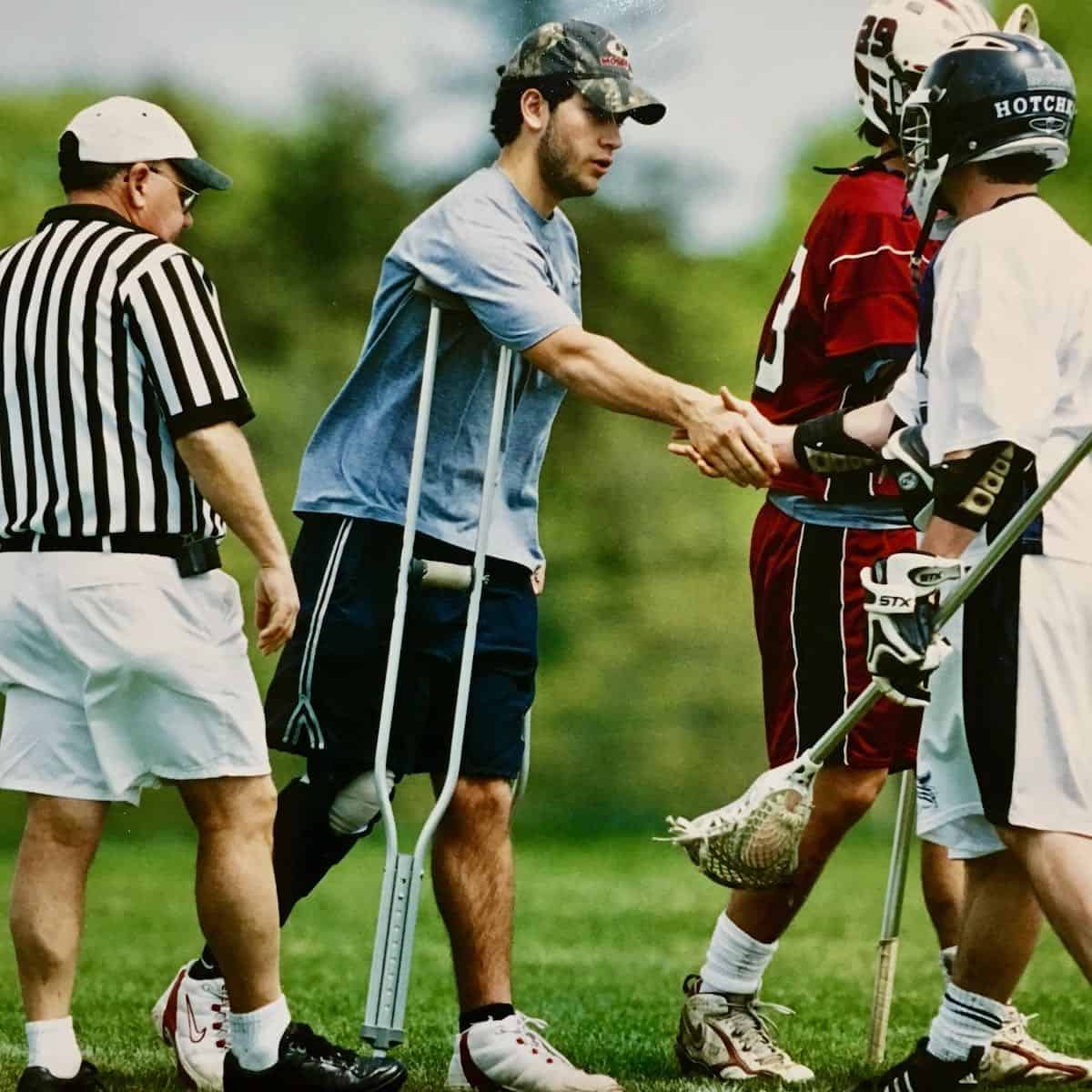 my son, on crutches, shaking hands on lacrosse field