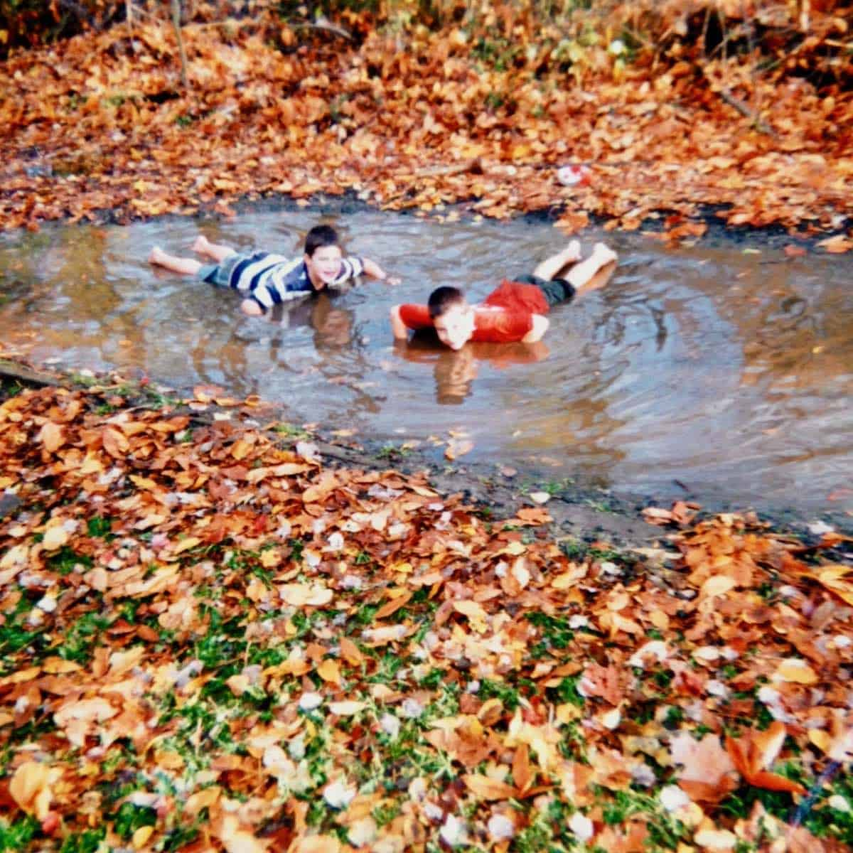 the boys playing in mud puddle